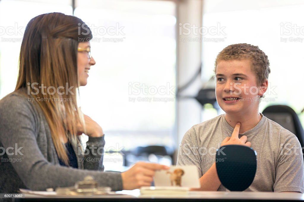 Teenage boy doing a vocal exercise for speech therapy stock photo