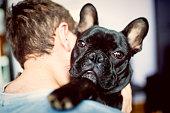 Teenage boy embracing his friend French Bulldog
