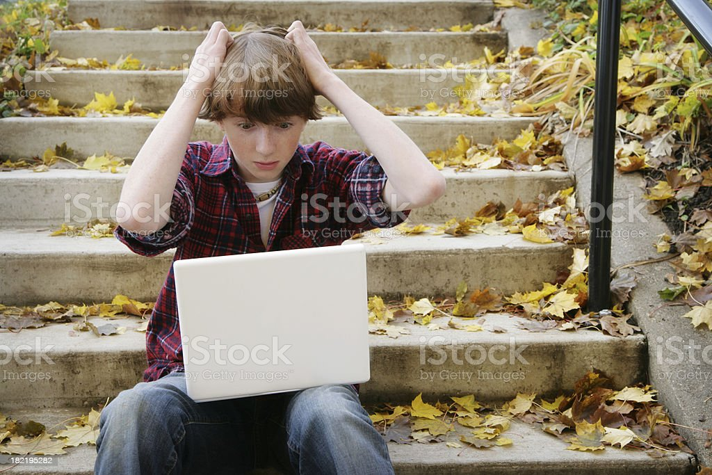 Teenage Boy Frustrated While Using Computer in Nature royalty-free stock photo