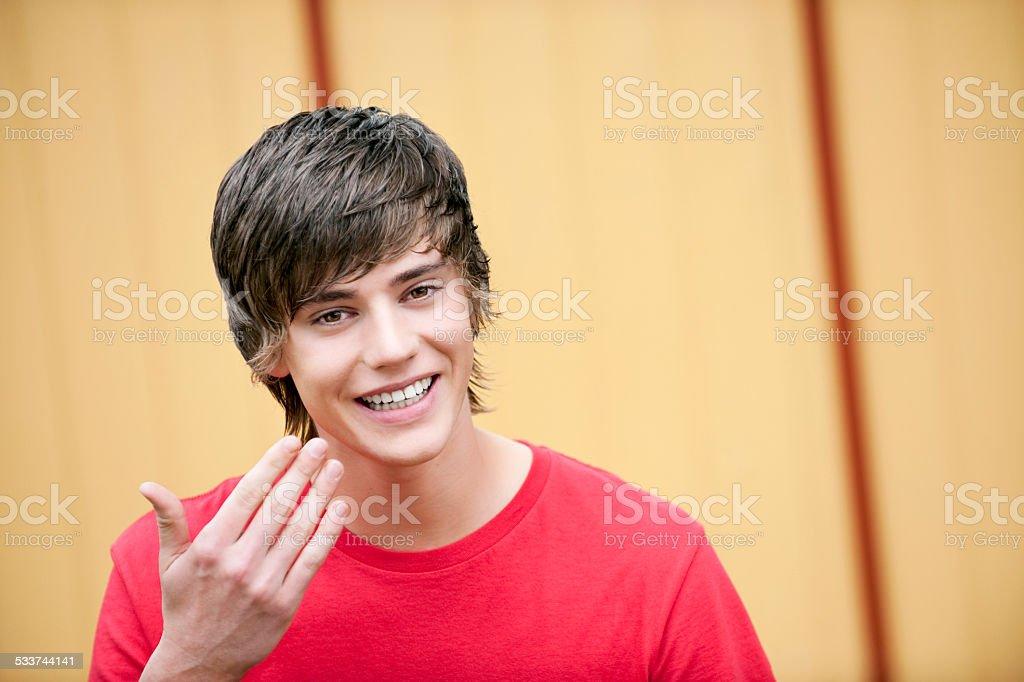 Teenage boy gesturing smiling stock photo