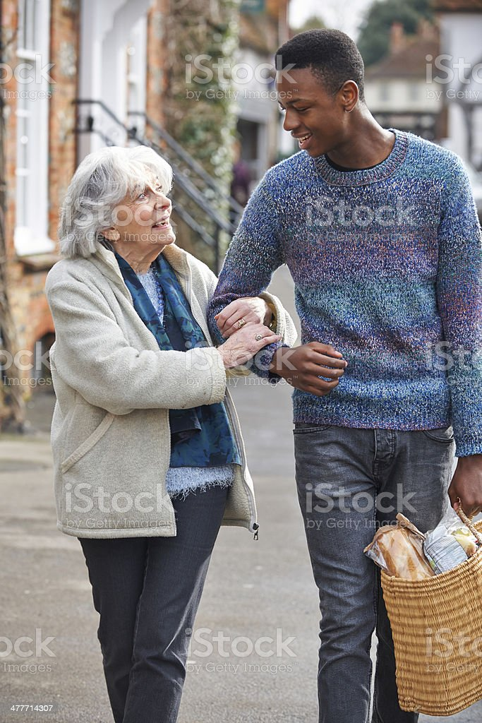 Teenage Boy Helping Senior Woman To Carry Shopping stock photo