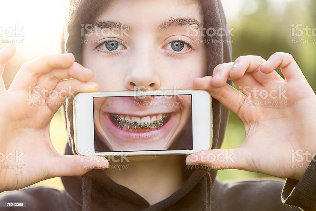 teenage boy holding a phone in front of his face stock photo