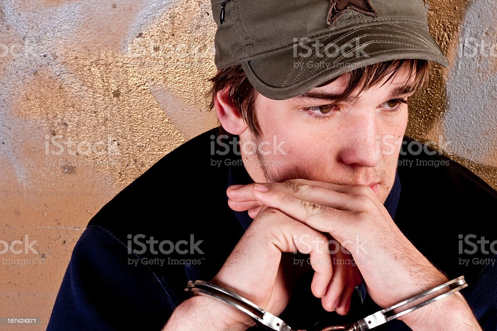 Teenage Boy in Handcuffs royalty-free stock photo