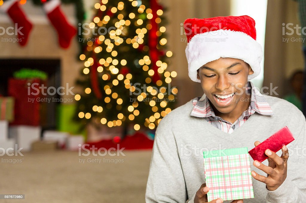 Teenage boy is surprised while opening Christmas gift stock photo