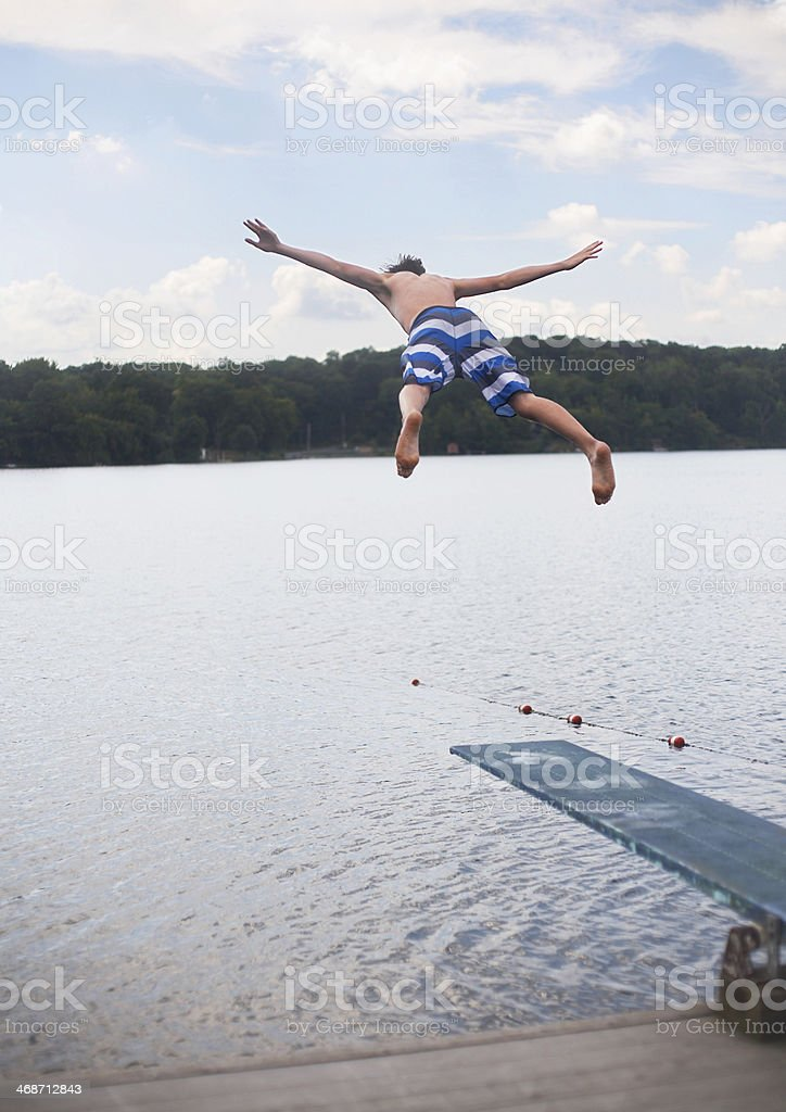 Teenage Boy Jumping into Sea stock photo