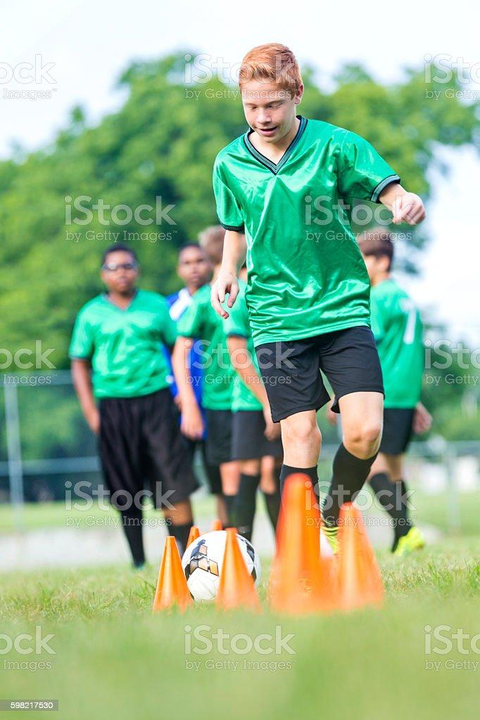 Teenage boy kicks soccer ball during practice stock photo