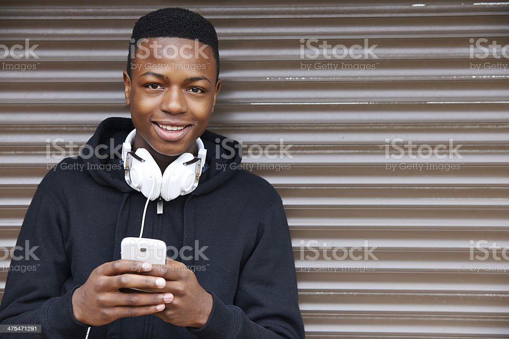 Teenage Boy Listening To Music And Using Phone stock photo