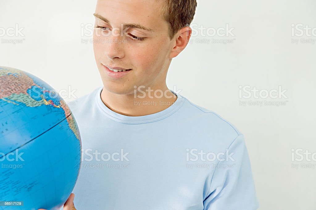 Teenage boy looking at a globe stock photo