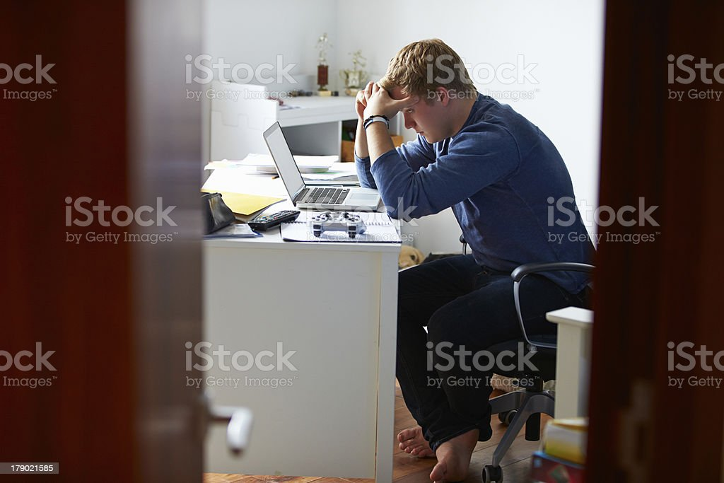 Teenage boy looking at laptop in bedroom looking stress stock photo