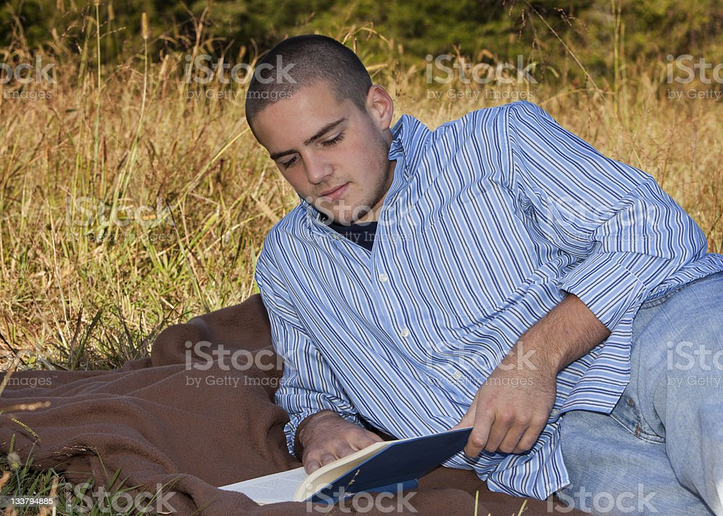 Teenage Boy Lying Outside Reading a Book stock photo