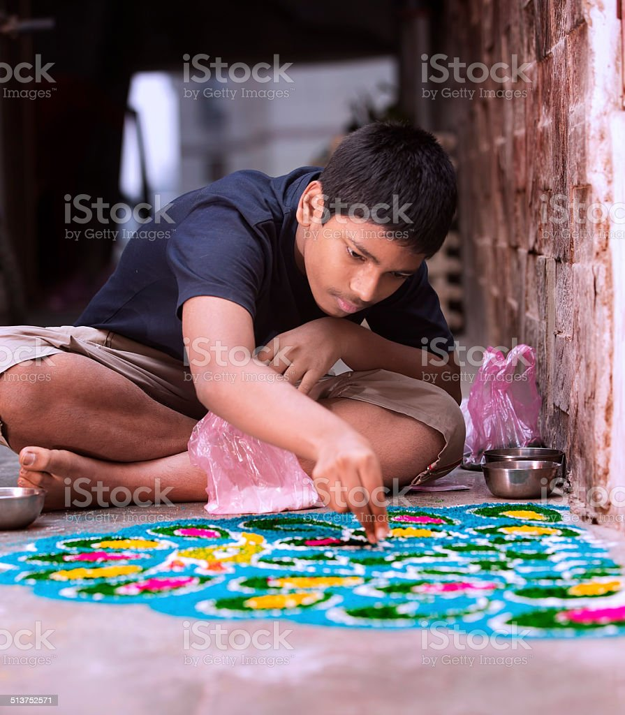 Teenage boy making Rangoli for Diwali stock photo