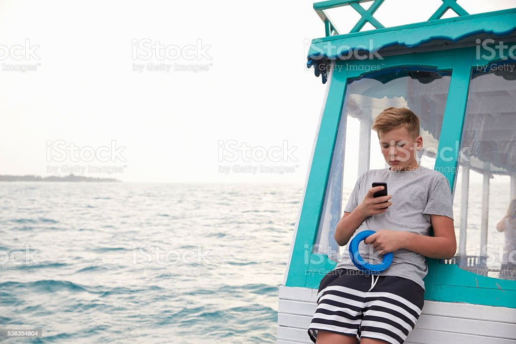 Teenage boy on boat using smartphone, ocean in the distance stock photo