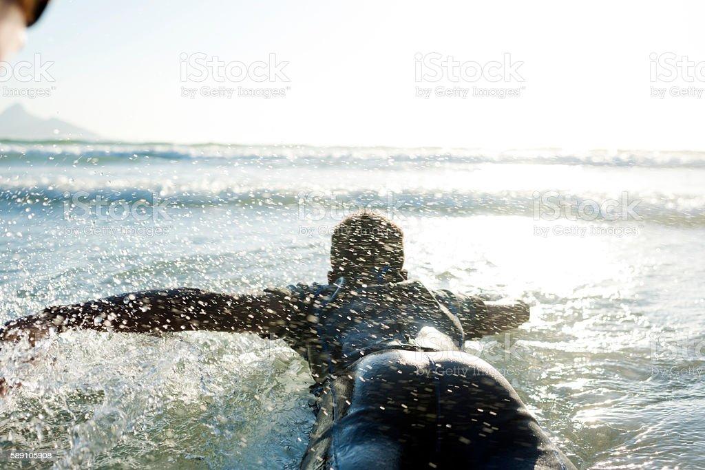 Teenage Boy Paddling Towards The Waves On His Surfboard stock photo