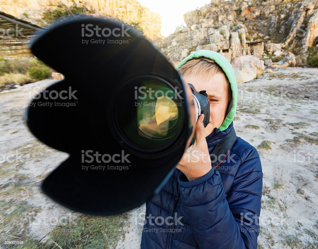 Teenage boy photographer using zoom lens in rocky surroundings stock photo