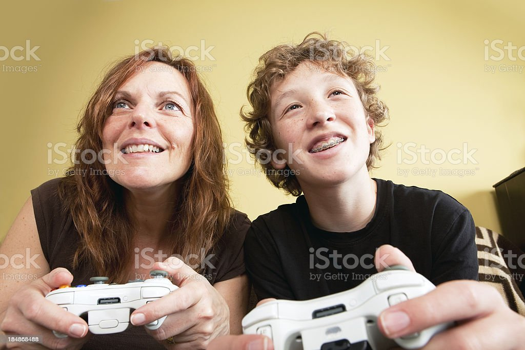 Teenage boy playing a video game with his mother royalty-free stock photo