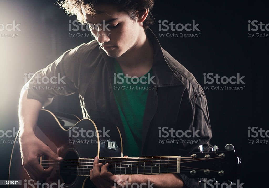 Teenage boy playing acoustic guitar on stage stock photo