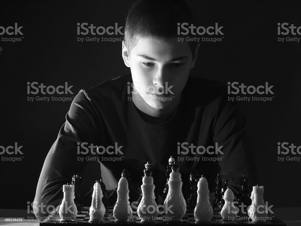 Teenage boy playing chess stock photo
