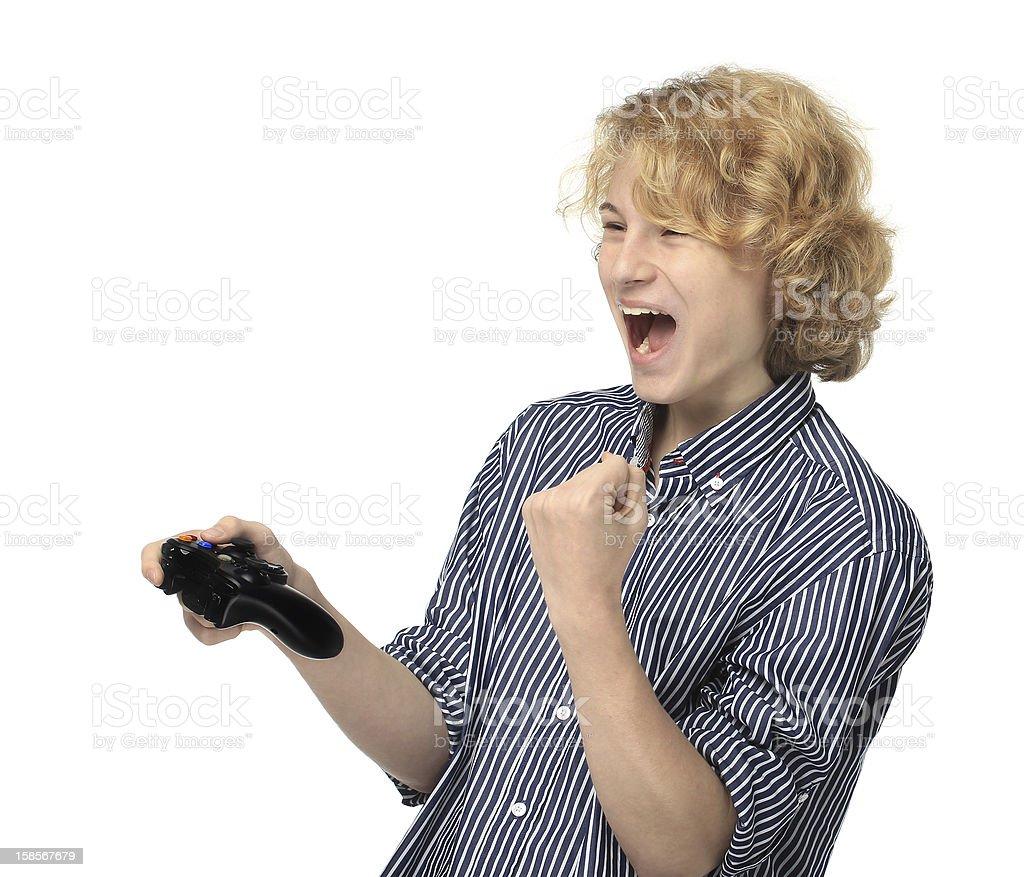 Teenage boy  playing  game,   pumps his fist.Winning royalty-free stock photo
