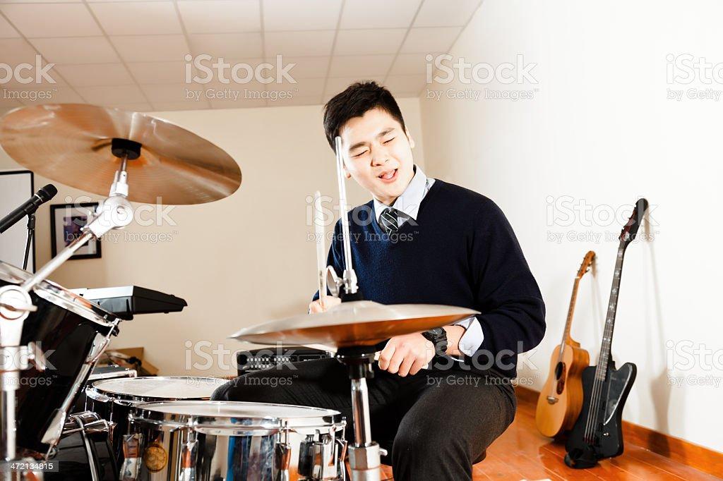 teenage boy playing on a drum set stock photo