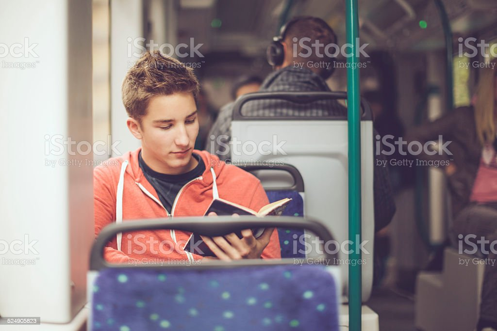Teenage boy reading a book on the tram stock photo