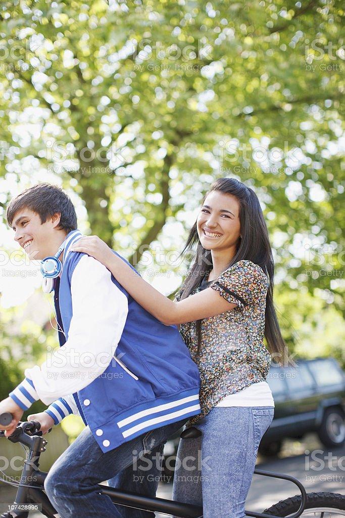 Teenage boy riding girlfriend on bicycle stock photo