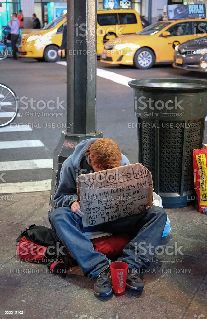 Teenage boy seen asking for charity in New York City stock photo