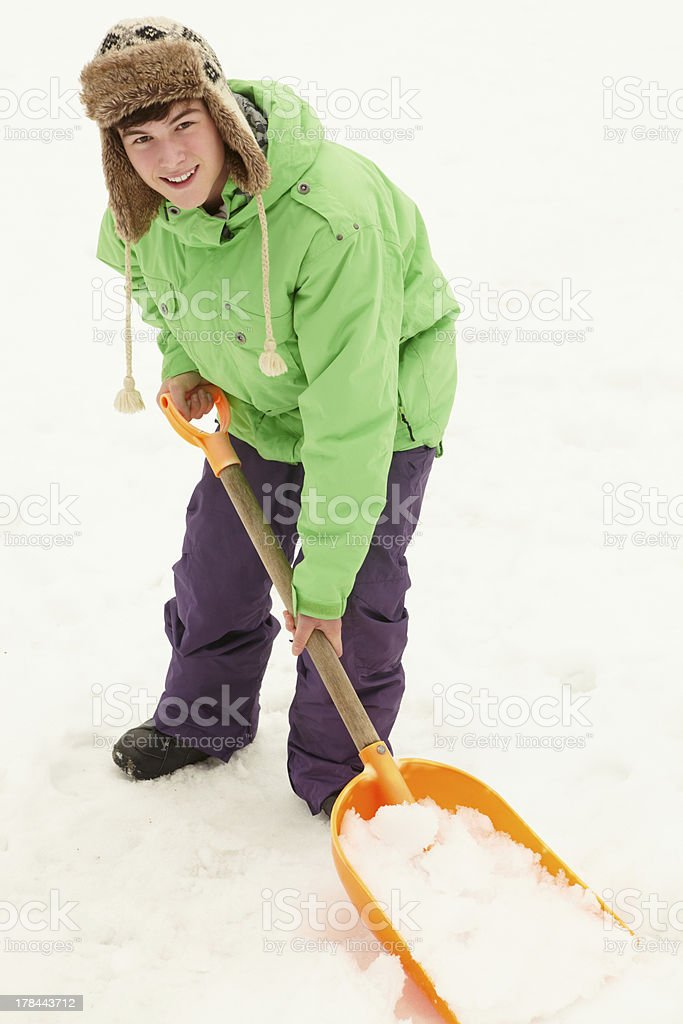 Teenage Boy Shovelling Snow From Path stock photo
