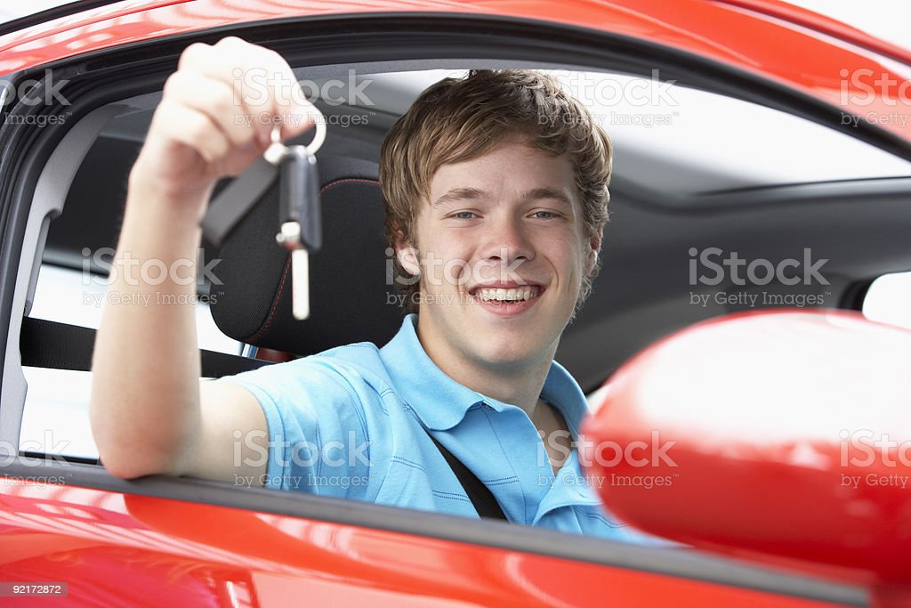 Teenage Boy Sitting In Car Holding Keys stock photo