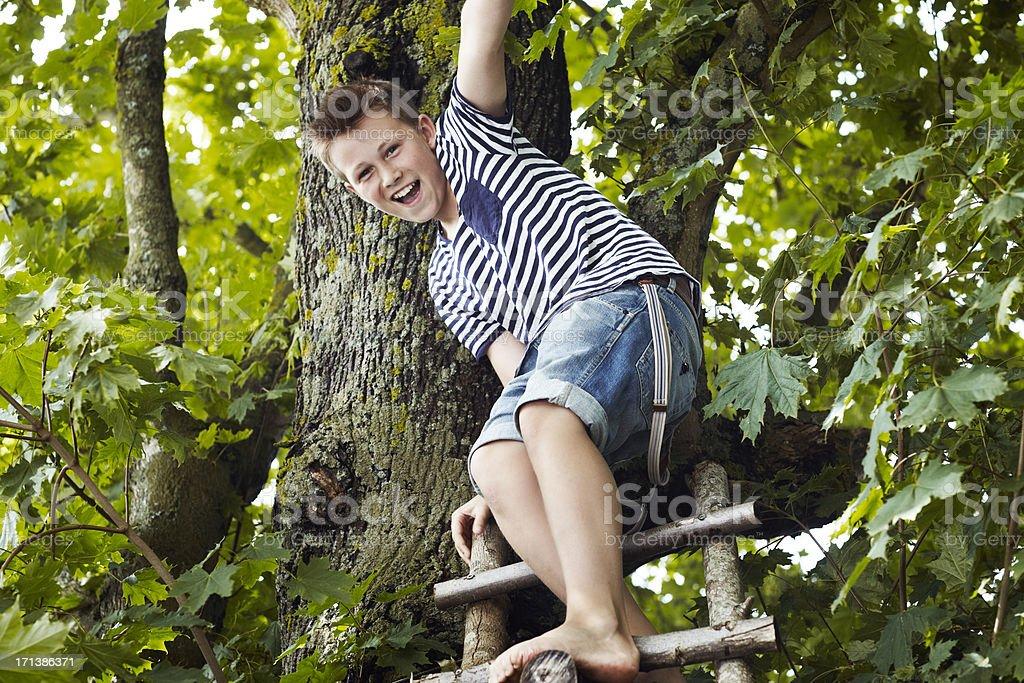 Teenage boy sitting on a wooden ladder stock photo