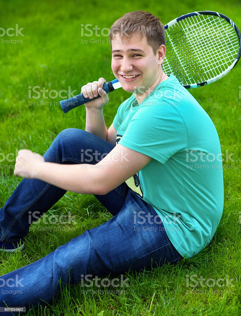 Teenage boy smiling while holding a tennis racket stock photo