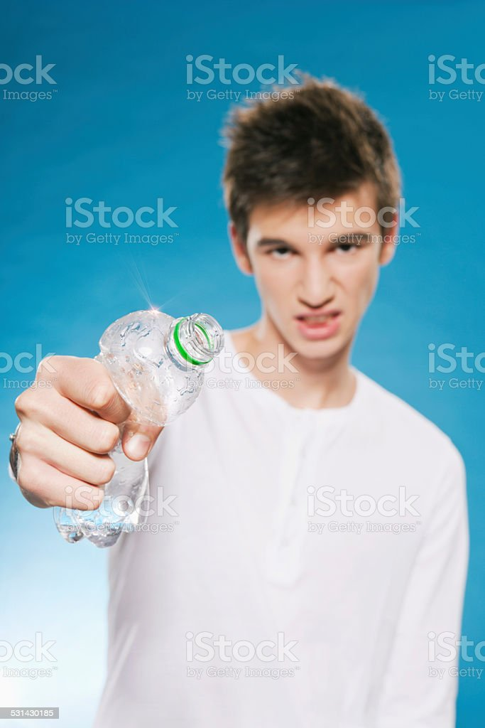 Teenage boy squashing empty plastic bottle recycling stock photo
