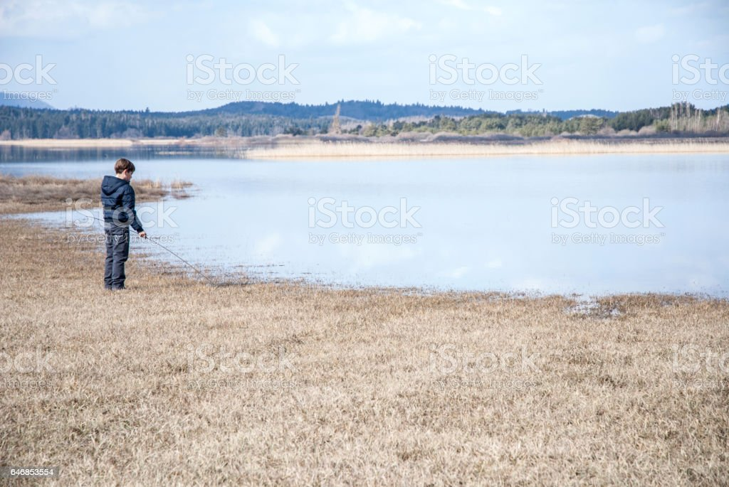 Teenage Boy Standing by the Lake stock photo