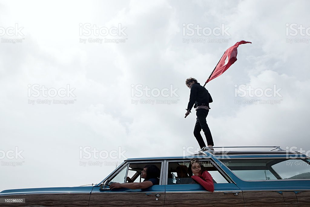 Teenage boy standing on top of car with flag royalty-free stock photo