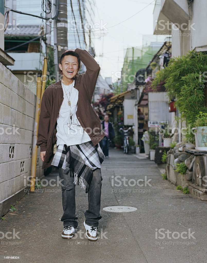Teenage boy (16-18) standing outdoors, laughing, portrait royalty-free stock photo