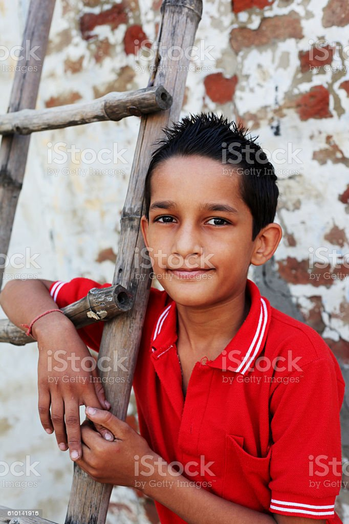 Teenage boy standing with ladder stock photo