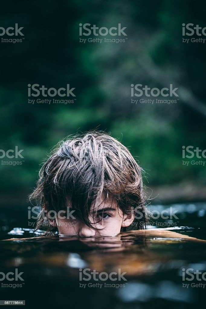Teenage Boy Submerge In A Dark Lake stock photo
