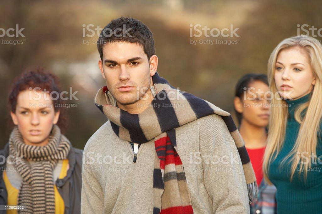 Teenage Boy Surrounded By Friends In Outdoor Autumn Landscape royalty-free stock photo