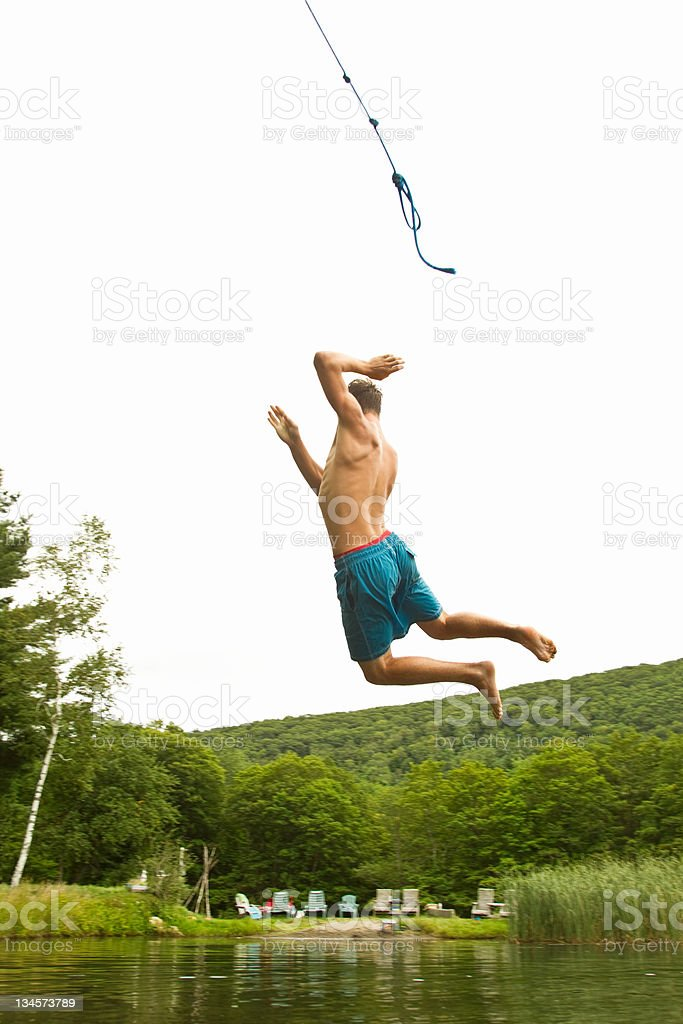 Teenage boy swinging off a rope into a lake stock photo