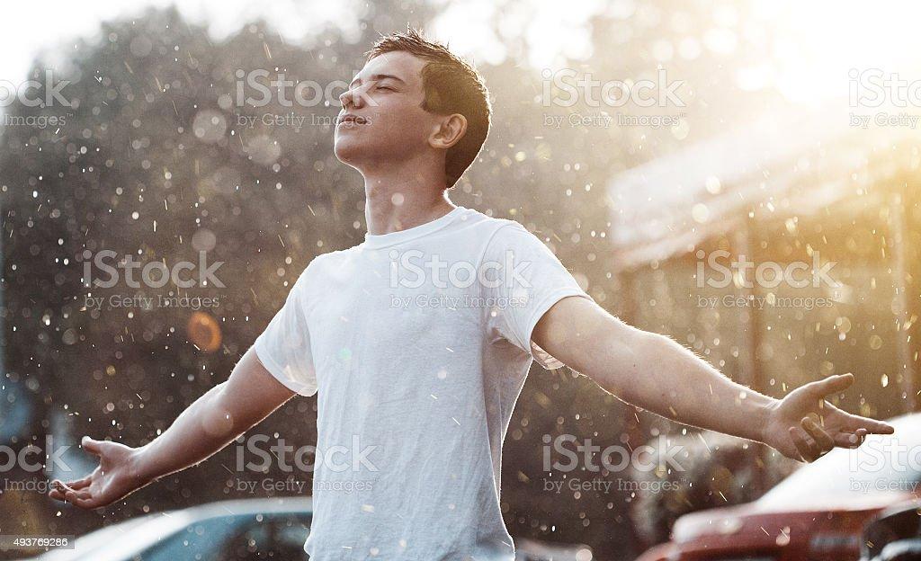 teenage boy under rain in the city stock photo