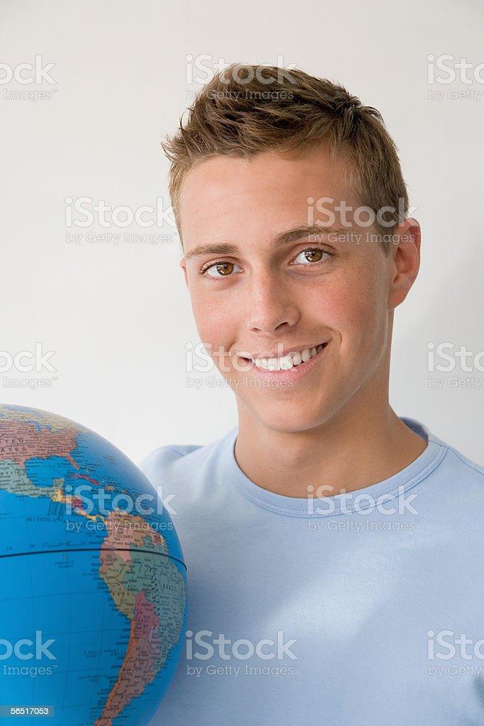 Teenage boy with globe stock photo
