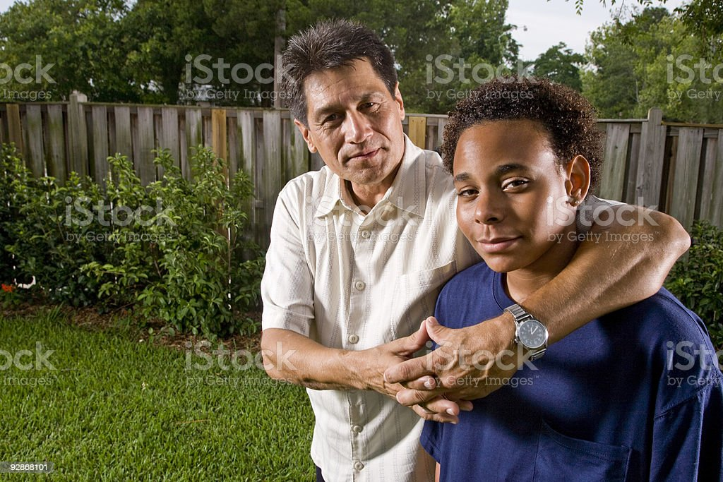 Teenage boy with his proud father's arm around him royalty-free stock photo