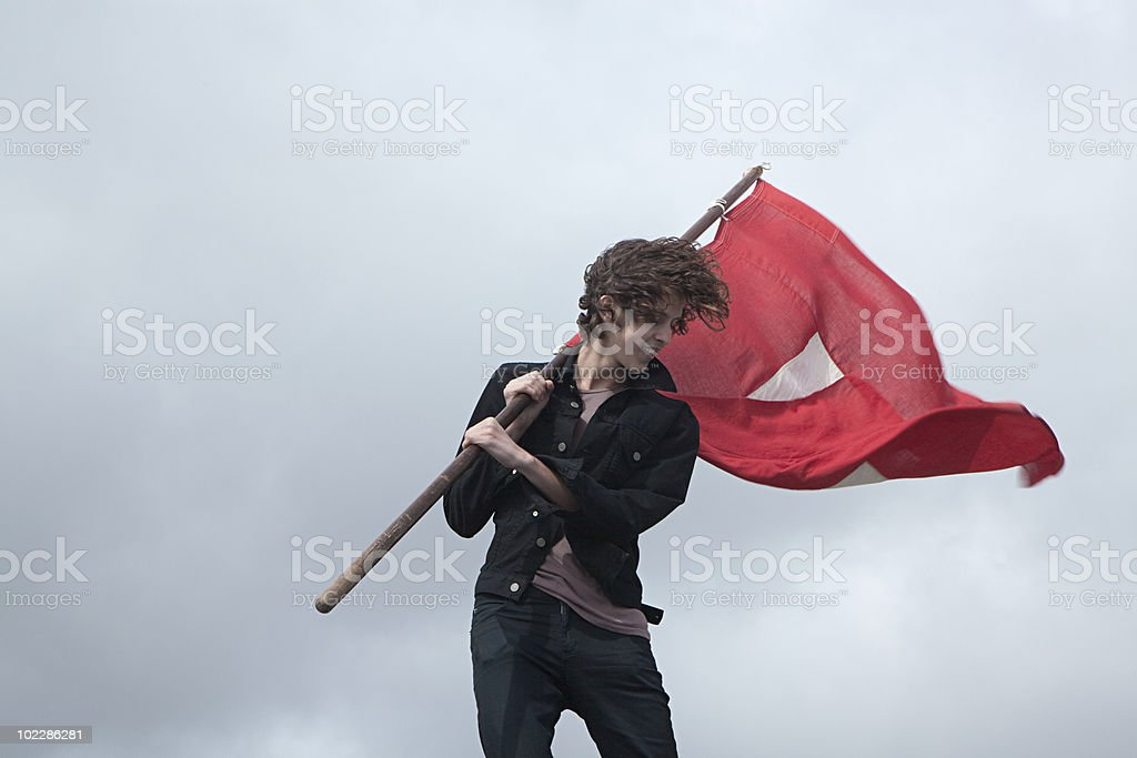 Teenage boy with red flag stock photo