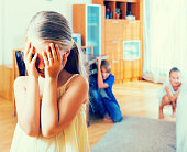 Teenage boy with sisters playing hide-and-go-seek