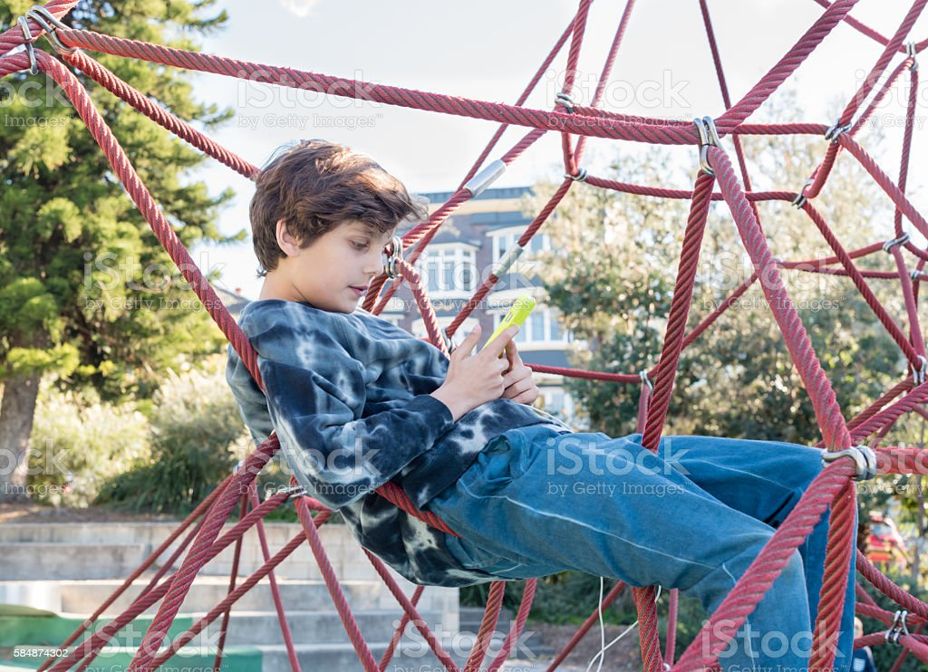 Teenage boy with smart phone in climbing frame stock photo