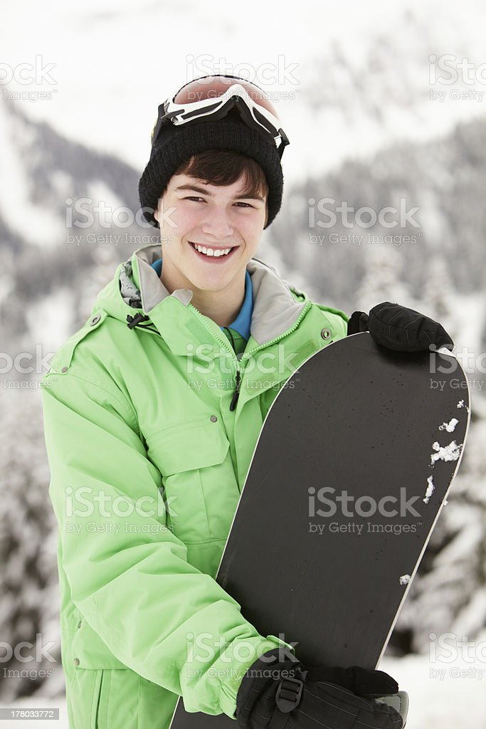 Teenage Boy With Snowboard On Ski Holiday In Mountains stock photo