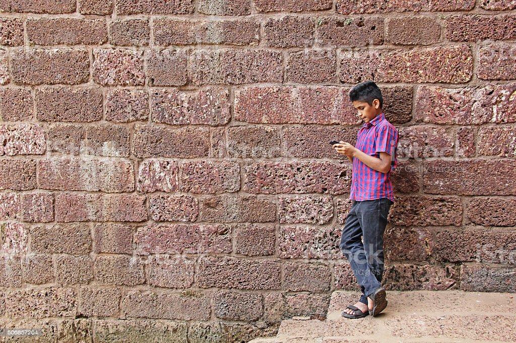 Teenage Boy Working on Smartphone stock photo