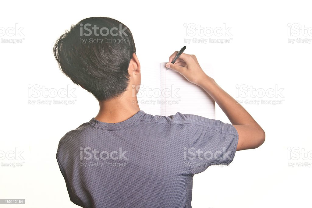 Teenage Boy writing on a blank page notebook stock photo