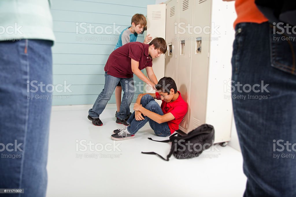Teenage boys bully classmate in school hallway. stock photo