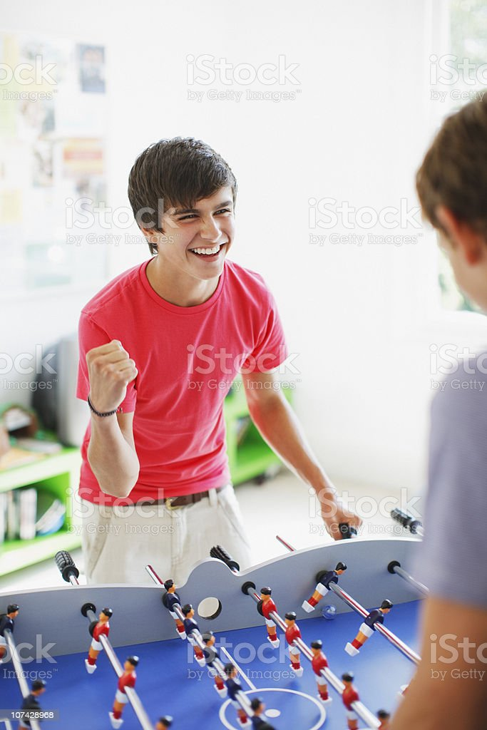 Teenage boys playing foosball together royalty-free stock photo