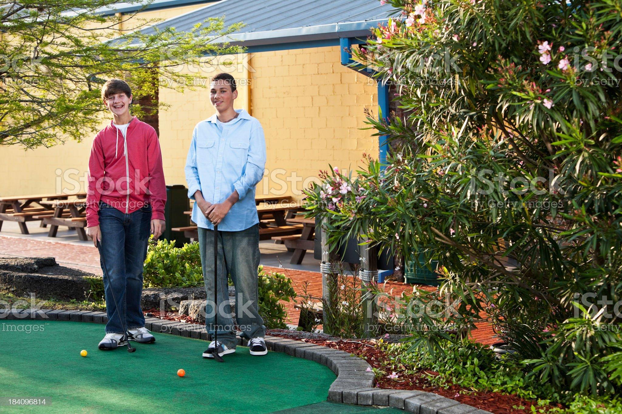 Teenage boys playing miniature golf royalty-free stock photo